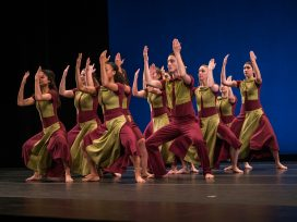 Student dancers of CODA company perform onstage in read and gold costumes.