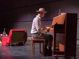 A male student plays the piano on a stage with a couch and props in the background.