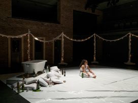 A student actor sits on a stage covered in a white tarp with a bathtub and pile of wine bottles in the background.