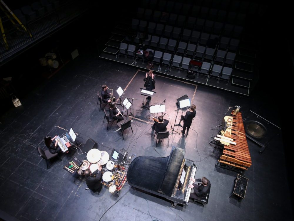 A music ensemble is seen from above rehearsing in an empty theater space with a conductor, piano, keyboard, drum set, saxophone, flute, violin, and singer.