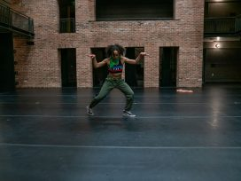 A female hip-hop dancer performs on the stage in the '62 Center for Theatre and Dance, backed by a brick wall.