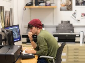 A male student in a red hat works with a design program on the computer in an art studio.